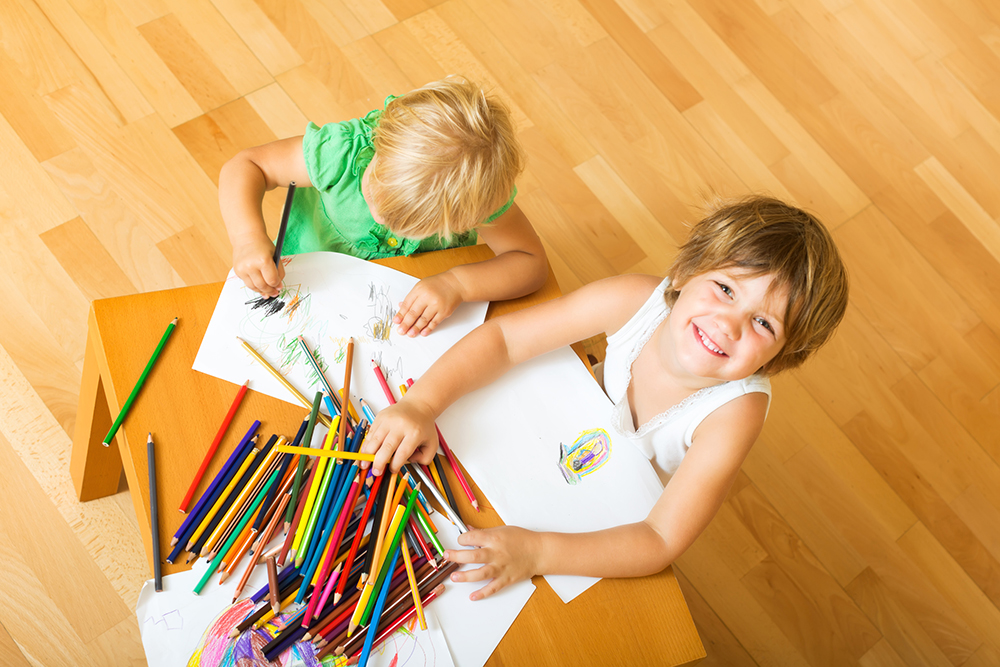 Two little children sketching with paper and pencils at home