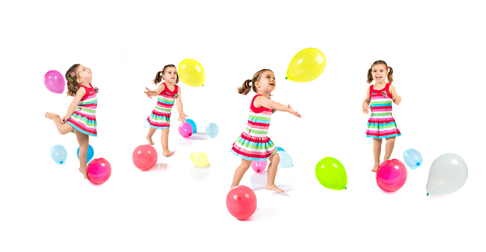 Kid playing with balloons over white background